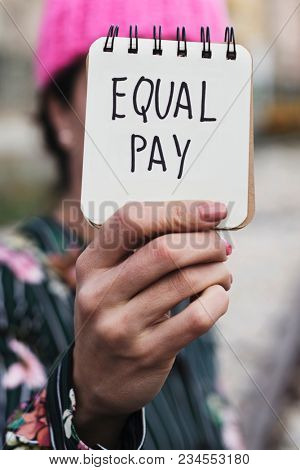 closeup of a young woman outdoors wearing a pink pussycat hat showing a notepad in front of her face with the text equal pay written in it