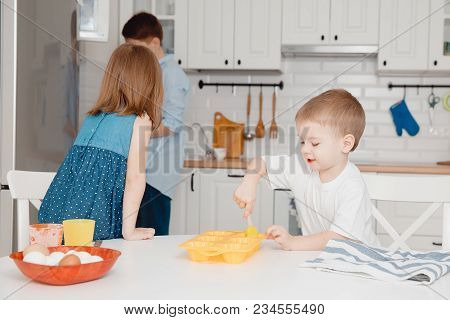 Young Family Cooking In The Kitchen. Happy Children, Sister And Brother Smile, Laugh, Lubricate The