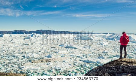 Travel in arctic landscape nature with icebergs - Greenland tourist man explorer - tourist person looking at amazing view of Greenland icefjord - aerial video. Man by ice and iceberg in Ilulissat.