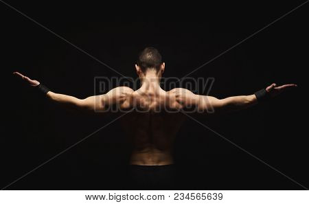 Unrecognizable man bodybuilder shows strong hands and back muscles, athletic trapezius. Low key, studio shot on black background, back view poster
