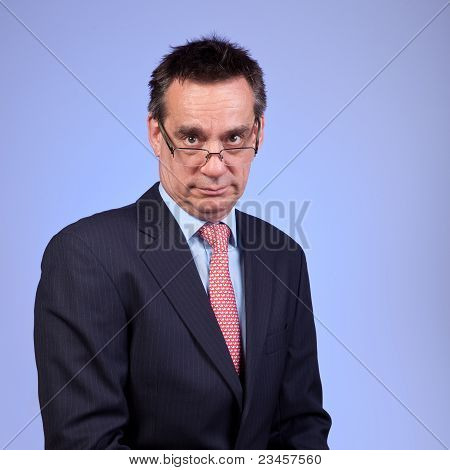 Grumpy Frowning Middle Age Business Man in Suit Looking over Glasses