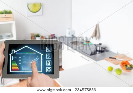 smart home and technology concept - close up of male hands pointing finger to tablet pc computer with house settings on screen over kitchen background