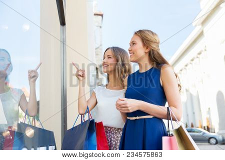 sale, consumerism and people concept - happy young women with shopping bags pointing finger to storefront