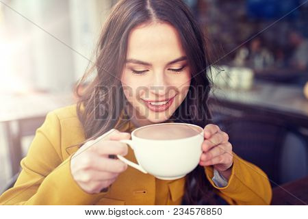 drinks and people concept - happy young woman or teenage girl with cup drinking delicious cocoa at city street cafe terrace