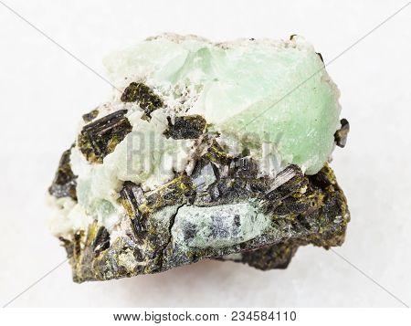 Macro Shooting Of Natural Mineral Stone Specimen - Epidote Crystals On Prehnite Stone On White Marbl