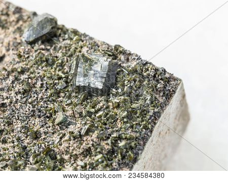 Macro Shooting Of Natural Mineral Stone Specimen - Crystals Of Epidote Close Up On Stone On White Ma