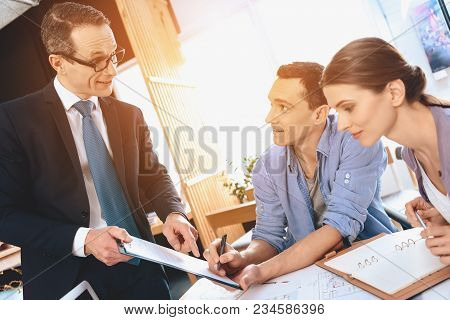 Realtor In Suit Sitting At Desk In Office. Father Is Signing Document For New Apartment.