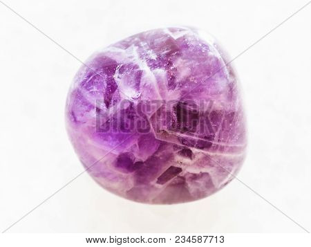 Macro Shooting Of Natural Mineral Rock Specimen - Tumbled Amethyst Gem On White Marble Background