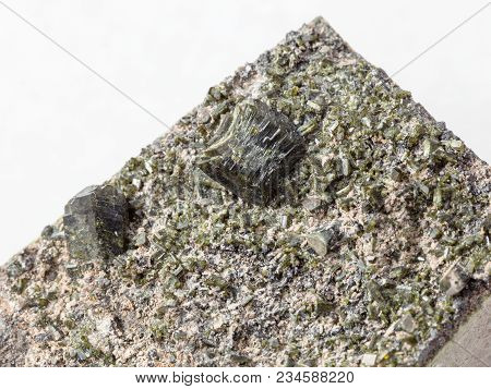 Macro Shooting Of Natural Mineral Stone Specimen - Crystals Of Epidote Close Up On Rock On White Mar