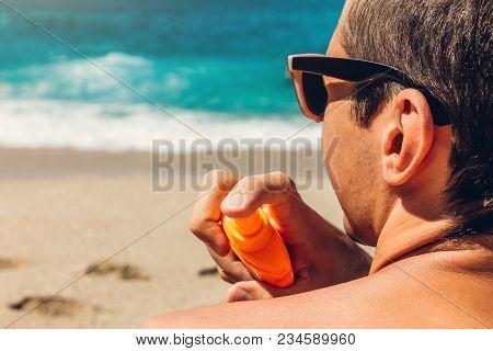 Sun Cream Protection. Man Sprays Sun Cream On His Shoulder On Beach. Skin And Body Care Concept. Hea