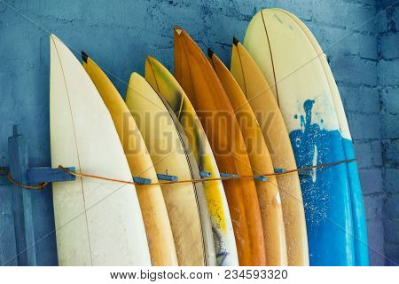 Set Of Different Color Surf Boards In A Stack By Ocean.bali, Indonesia. Surf Boards On Sandy Weligam