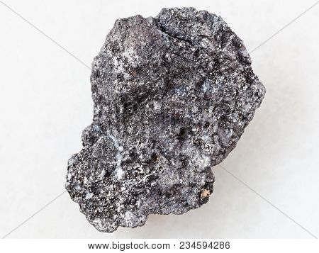 Macro Shooting Of Natural Mineral Rock Specimen - Piece Of Graphite Stone On White Marble Background