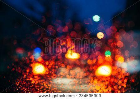 Blurred Car Light Trough Wet Glass. Wet Drops On Glass.