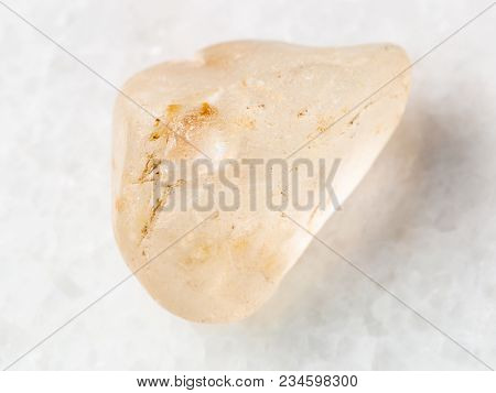 Macro Shooting Of Natural Mineral Rock Specimen - Tumbled Topaz Gemstone On White Marble Background