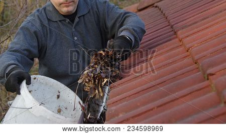 Man Cleaning Dirty Gutter From Moss And Leaves. Building With Unclean Tile Roof After Winter. Spring