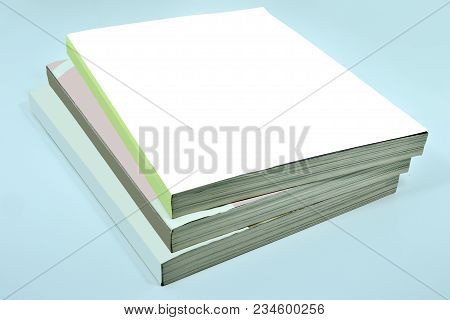 Stack Of Three Thick Magazines Or Book, Catalogs With A Blank White Soft Cover On A Blue Background