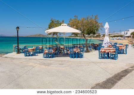 Naxos Greece - May 24, 2017 Tables With Chairs In Typical Greek Tavern With View On Sea Bay Near Agi