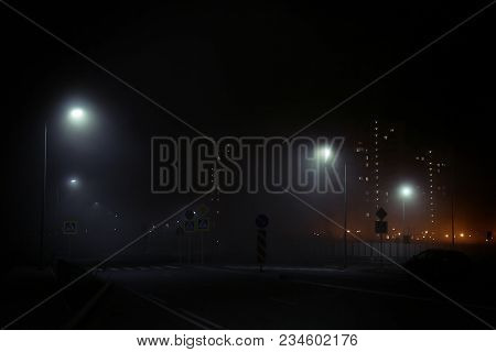 The Road At Night Illuminated By Dim Lanterns During A Thick Fog. Fog In The City. High Houses In Fo