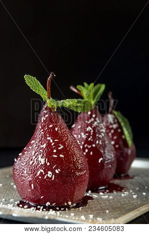 Pears In Wine. Row Of Raditional Dessert Pears Stewed In Red Wine On Black Background.