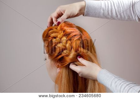 Beautiful, With Long, Red-haired Hairy Girl, Hairdresser Weaves A  Braid, Close-up In A Beauty Salon