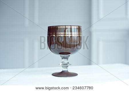 A Vintage Brown Crystal Wine Glass On Wooden Table. Brown Crystal Goblet On The Leg.