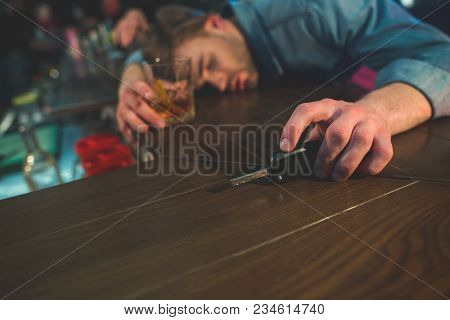 Drunk Driver Sleeping On Counter. He Holding Key In Hand. He Locating In Bar