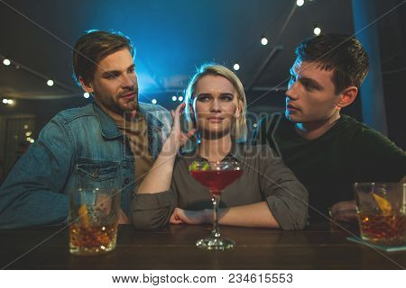 I Do Not Want To Tell About It. Portrait Of Disappointed Female Talking With Two Interested Guys. Ac