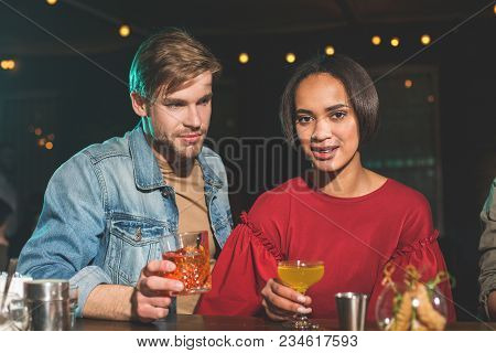 Portrait Of Beaming Girl Telling With Smiling Man While Tasting Cocktail. Beaming Lovers Relaxing In