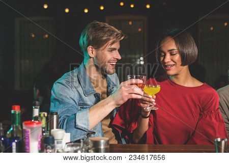 Happy male clanging glasses of alcohol beverage with cheerful female. Glad couple resting in bar concept poster