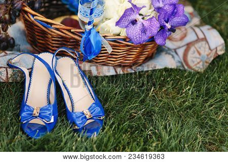 Bright Blue Female Sandals And A Basket With Blue Irises On A Juicy Green Grass. Lovely Blue Lady Sh