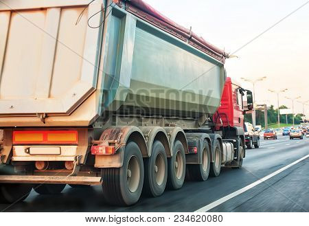 Big Dump Truck Goes In The Evening On Highway