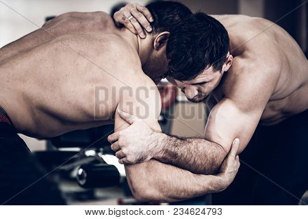 Two Strong Men Without Shirts Wrestling In Gym