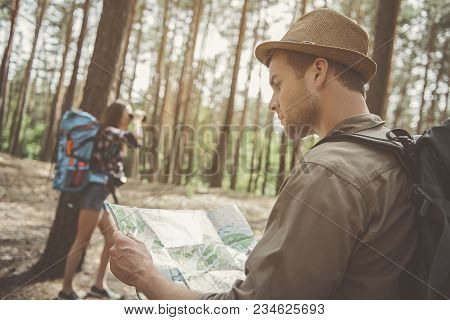 Where We Are. Side View Of Concentrated Young Man Is Standing In The Forest With His Girlfriend. He