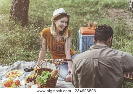 Man And Woman In Love Sitting On Rug Outside And Laughing. Guy Playing Melody On Musical Instrument