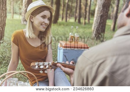 Happy Couple Having Picnic In Park. Guy Performing Pleasant Melody To Woman On Guitar. Woman Is Smil