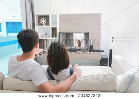 Happy Family Watches Television While Sitting On The Sofa In The Morning.