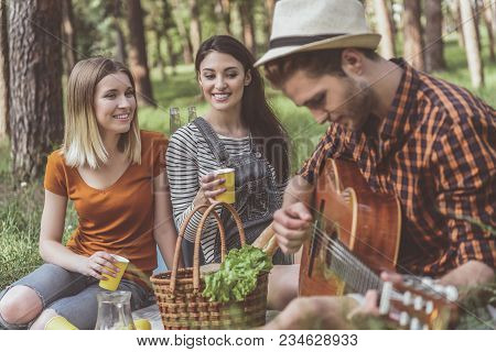 Talented Man Playing The Guitar. Two Women With Cups In Hands Admiring The Performance Of Melody. Th