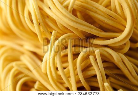 Close Up (macro) Of Dry, Uncooked Egg Noodles, Curling And Intertwined. Shallow Depth Of Field.