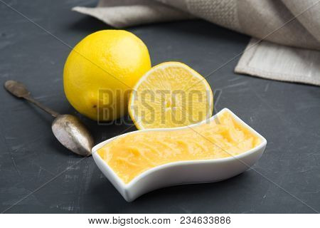 Closeup View Of Lemon Cream (curd) In White Jar With Tissue And Spoon On Dark Background