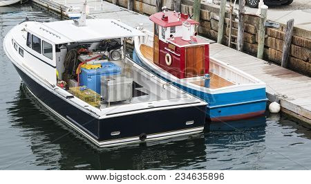 A Real Boat That Looks Like A Toy Tug Boat Is Tied To A Dock And Another Boat In Rockland Maine