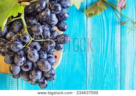 Grapes On A Blue Wooden Table. Branch Of Fresh Ripe Red Grapes. Beautiful Background With A Branch O