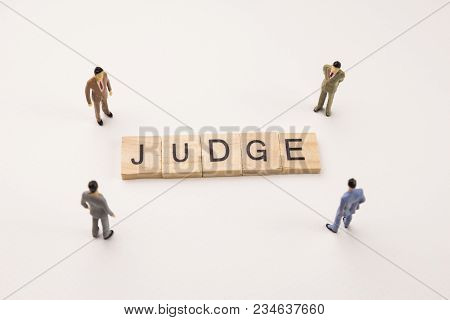 Miniature Figures Businessman : Meeting On Judge Letters By Wooden Block Word On White Paper Backgro
