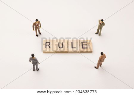 Miniature Figures Businessman : Meeting On Rule Letters By Wooden Block Word On White Paper Backgrou
