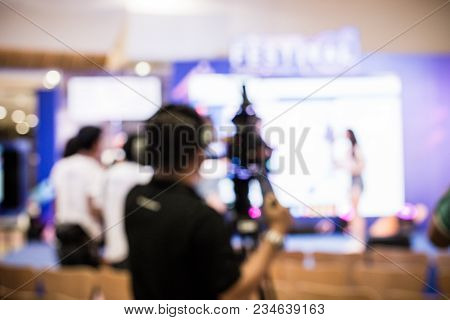 Blurred Image Of Young Cameraman Using A Professional Camcorder In Door At Event Filming Music Show