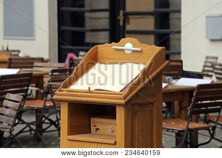 Wooden Rostrum With Menu At Restaurant Terrace