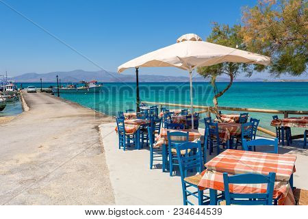 Naxos, Greece - May 22, 2017: Tables With Chairs In Typical Greek Tavern With View Of Sea Bay. Agia