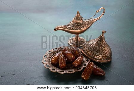 Bronze plate with dates  and aladdin lamp on dark green wooden background. Ramadan background. Ramadan kareem.