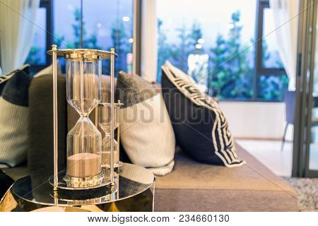 A hourglasss side pillows on a brown sofa with a black and white pillows background in livingroom. poster