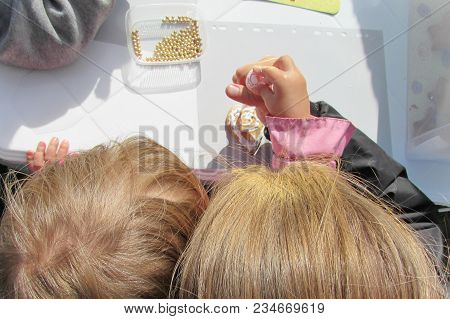 A Child With His Mother Decorate With Glaze And Gold Beads A Small Gingerbread
