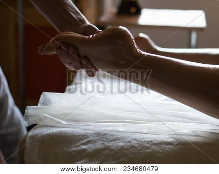 Professional Masseur Doing Kneads Legs Of A Girl At Ayurveda Oiled Massage Session Room